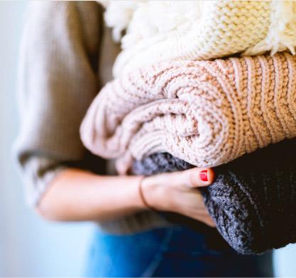 Herz statt Verstand: Frau mit Pullovern in der Hand | marx Design in Holz